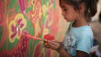 A refugee child paints a mural