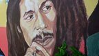 "a mural depicting reggae music icon Bob Marley decorates a wall in the yard of Marley""s Kingston home in Jamaica"