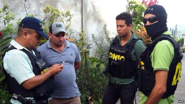 Police officers (in bullet-proof jackets) escort Plutarco Ruiz in Santa Barbara, Honduras, 18 November