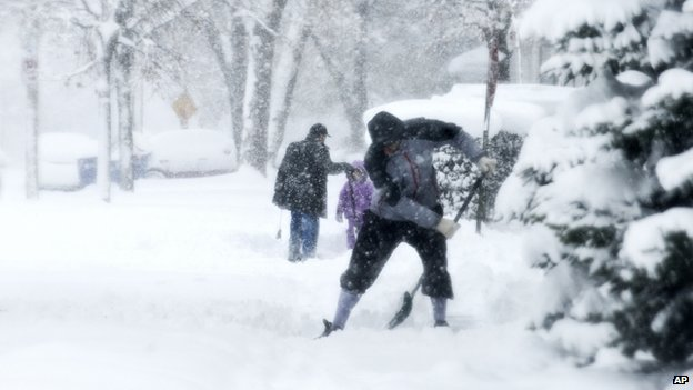 Residents shovel their sidewalks along Coit Avenue in the wind and snow in Grand Rapids, Mich.