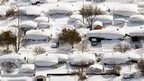 Homes and cars covered in snow