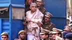 Controversial religious leader Sant Rampal stands by the door of a police van as he is brought to a court, surrounded by police personnel in Chandigarh, India, Thursday, Nov. 20, 2014.