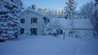 A wide scene of a house covered in snow, a thick blanket of snow over the roof of the house and the trees in the foreground.