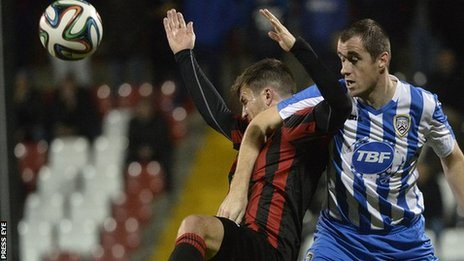 Crusaders striker Diarmuid O'Carroll is tackled by Coleraine's David Ogilby