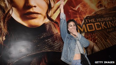 Woman uses three finger salute in front of Hunger Games movie poster