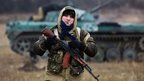 A rebel fighter stands in front of a captured Ukrainian tank at Ilovaisk, 18 November