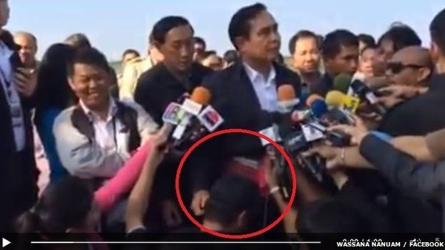 Thai prime minister surrounded by journalists, patting one on the head