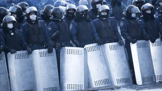 Riot police stand against protesters in Kiev on 24 January 2014