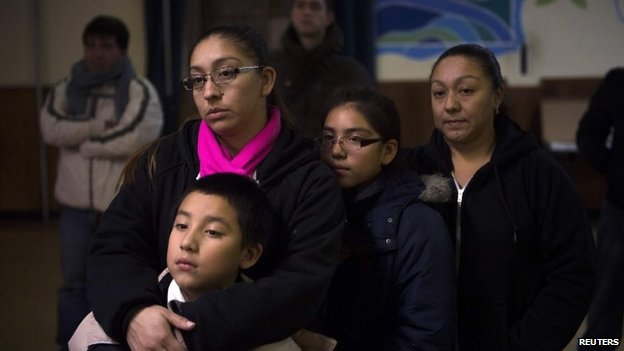 Undocumented immigrant Alejandra Mota, holds her son, a US citizen, as they watch President Barack Obama announce executive action on immigration, at the West Kensington Ministry church, in Philadelphia, November 20, 2014.