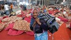 "An Indian follower of self-styled ""godman"" Rampal Maharaj carries her belongings inside the ashram at Barwala in the district of Hisar, some 175 kilometres (108 miles) north of New Delhi on November 20, 2014"