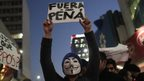 "A demonstrator wears a Guy Fawkes mask while holding a sign reading ""Pena (Mexico""s President Enrique Pena Nieto) Out"" during a protest in support of 43 missing Ayotzinapa students, in Monterrey November 20, 2014."