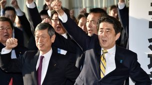 Japan's Prime Minister and leader of the ruling Liberal Democratic Party (LDP) Shinzo Abe (R) raises his fist in the air to shout with his party's lawmakers at the LDP headquarters in Tokyo on November 21, 2014 as the party opens an election campaign office.