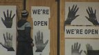 Close up of boarded entrance to Ferguson Market & Liquor store with signs saying 'We're open' and posters of pairs of hands