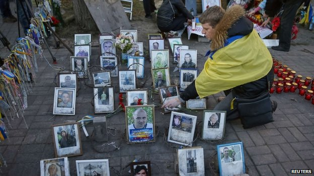 A man looks at photos in Kiev of people who were killed trying to overthrow President Yanukovych (21 November 2014)