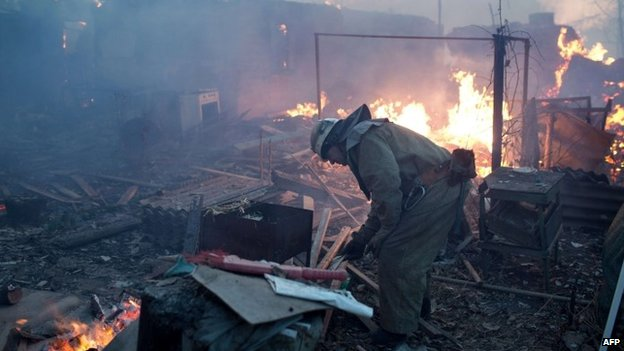 A fire fighter at work in the flashpoint eastern Ukrainian city of Donetsk after shelling reportedly destroyed several houses (20 November 2014)