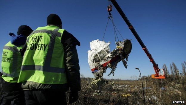 Investigators watch as a piece of wreckage from the Malaysia Airlines flight MH17 is transported from the site of the plane crash in the Donetsk region, eastern Ukraine (20 November 2014)