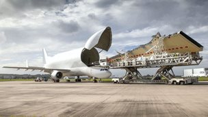 A Beluga opens its cargo bay door to transport a wing