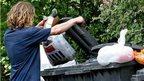 Person putting rubbish in a bin