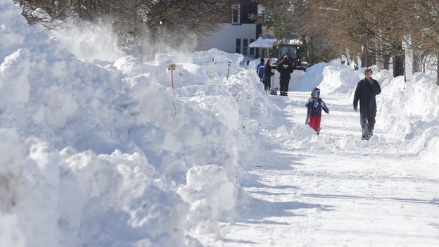 People walking in snow covered street in Buffalo, New York