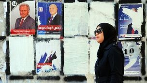 A woman walks past a wall plastered with electoral campaign posters in Tunis, Tunisia. Photo: 21 November 2014