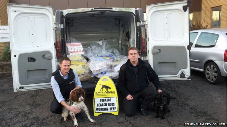 Officers pose with the sniffer dogs with the haul from the raids