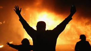 Demonstrators celebrate as a business burns after it was set on fire during rioting following the grand jury announcement in the Michael Brown case in Ferguson, Missouri (25 November 2014)