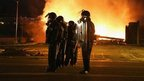 Police officers watch as a business burns after it was set on fire during rioting