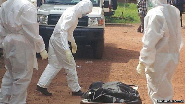 People look at a body outside hospital in Kenema