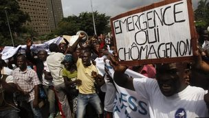 Demonstrators cover their faces from tear gas fired by security forces during a protest by workers affected by the government's closure of plastic bag production and factories in Abidjan on November 25, 2014