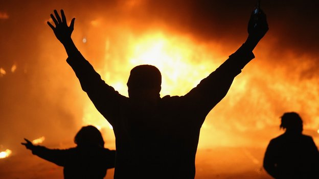 A protestor is silhouetted against a fire in Ferguson, Missouri.