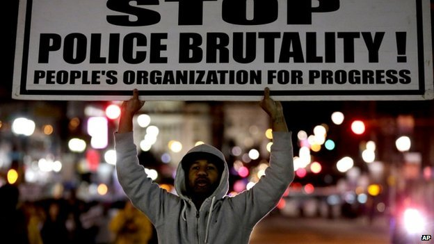 """A protester holds a sign reading """"stop police brutality"""" at a protest in Newark, New Jersey, on 26 November 2014"""