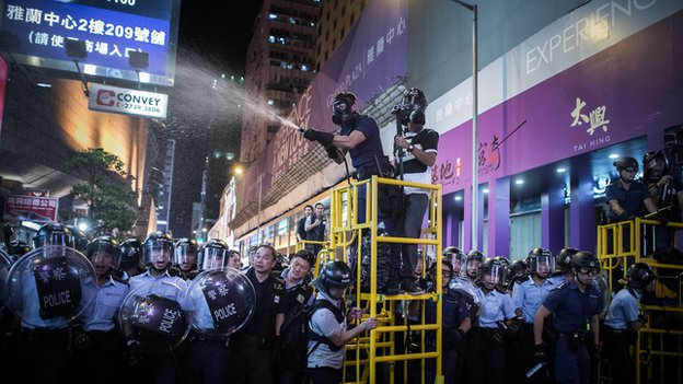 Police use pepper spray as they clear a road at a pro-democracy protest site in the Mongkok district of Hong Kong on November 25, 2014