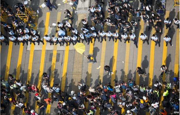 A lone pro-democracy demonstrator (C) carries a yellow umbrella in front of a line of policemen in Mongkok, Hong Kong, China, 26 November 2014.