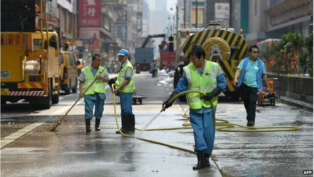 Workers spray a road, previously occupied by pro-democracy protesters, after police completed their clearance of a major protest site in the Mongkok district of Hong Kong on 26 November 2014