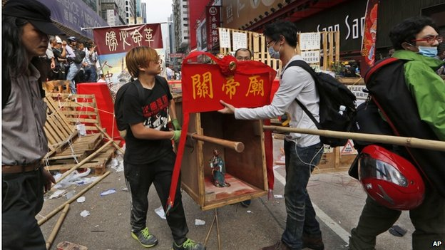 Protesters remove the Chinese Taoist God of War, Guan Yu, set up at a barricade at an occupied area as police keep clearing away them in Mong Kok district of Hong Kong Wednesday, 26 November 2014.