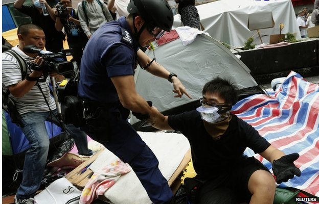 A riot police officer detains a pro-democracy protester who refuses to leave during the clearance of a protest site on the main Nathan Road at Mongkok district in Hong Kong November 26, 2014