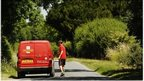 A postman returns to his Royal Mail delivery vehicle
