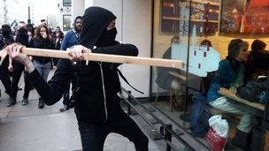 A protester about to hit a window of Starbucks with a piece of wood, 19 November 2014