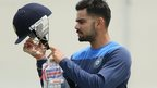 Player inspects cricket helmet