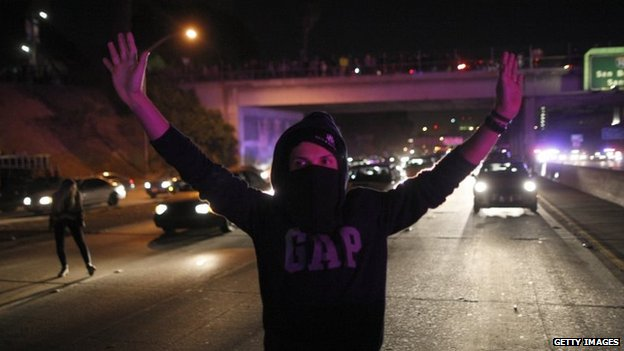 A man is illuminated by the lights of approaching police vehicles as protesters set up barricades and shut down the 101 freeway in Los Angeles, California, 25 November 2014