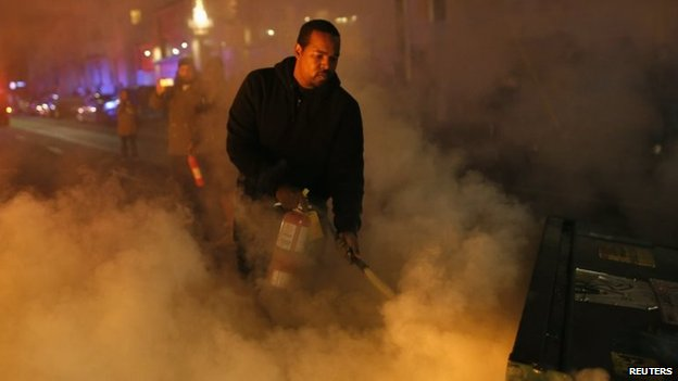 A local resident attempts to extinguish a street fire set by protesters in Oakland, California, 25 November 2014