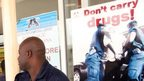 A security in front of an anti-drug trafficking poster outside Kotoka International Airport, in Accra  - 2007