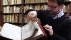 Remy Cordonnier opens a page of  Shakespeare's original first folio.