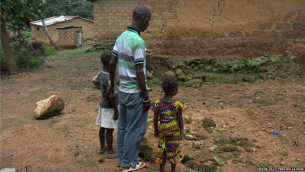 family stands over Ebola grave