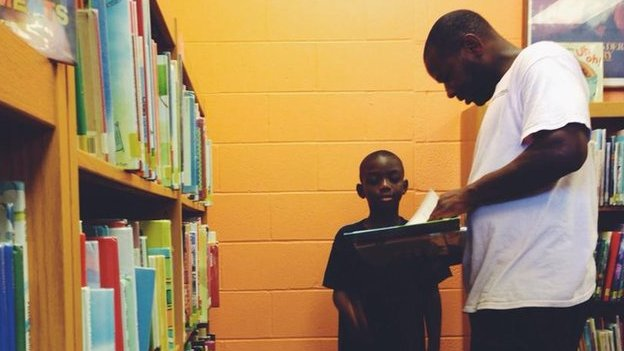 A father and son in a library