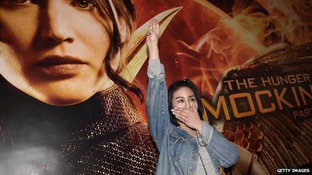 A protestor displays a Hunger Games-inspired salute.