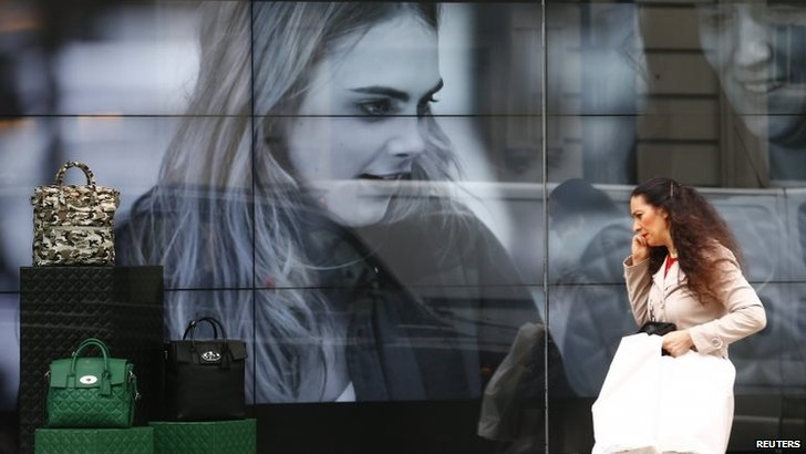 A woman walks past a video display in the shop window of a Mulberry store in central London