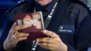 A Border Force officer checking passports at Terminal 2, Heathrow Airport in June