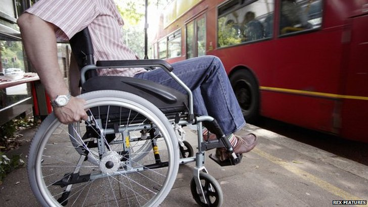 Man in wheelchair waiting for bus