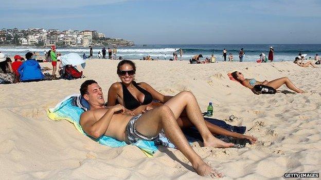 A couple enjoy the sun on Bondi Beach in Australia